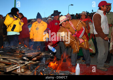 LA PAZ, BOLIVIA, 21st June. A male Aymara amauta or spiritual leader sprinkles an offering of alcohol onto a fire - Stock Photo