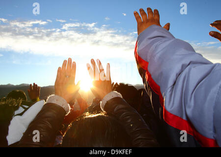 LA PAZ, BOLIVIA, 21st June. Bolivians hold up their hands to receive the warmth and energy of the rising sun at - Stock Photo