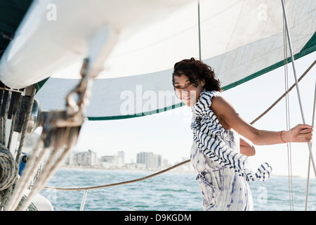 Young woman on yacht wearing striped scarf - Stock Photo