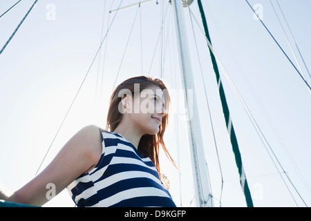 Young woman on yacht wearing striped top - Stock Photo