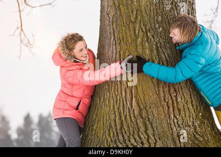 Mid adult couple hugging tree - Stock Photo