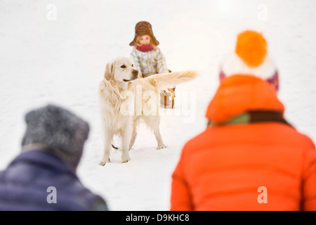 Daughter with dog looking at parents in foreground - Stock Photo