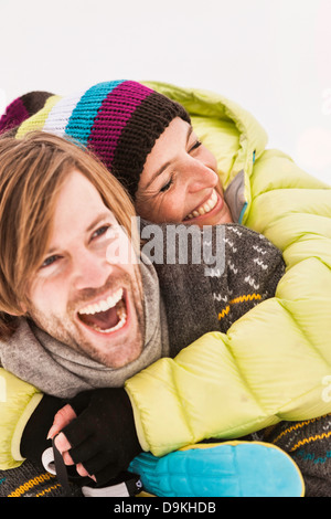 Mid adult couple embracing, woman wearing knit hat - Stock Photo