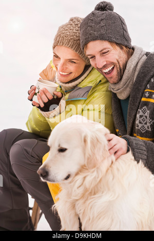 Mid adult couple wearing knit hats with dog - Stock Photo