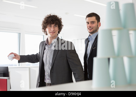 Office workers throwing paper at disposable cups - Stock Photo