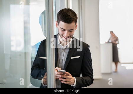 Businessman using cell phone, woman in background - Stock Photo