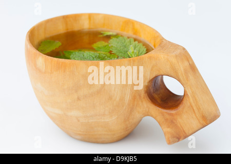 Hand Carved Wooden Kuksa Containing Lemon Balm (Melissa officinalis) Herbal Tea - Stock Photo