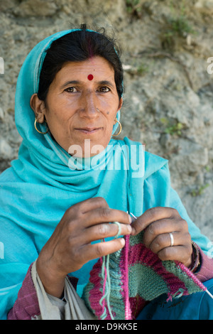 A Gaddi tribeswoman knits a garment while posing for the camera at the Himalayan village of Kugti in Himachal Pradesh, - Stock Photo