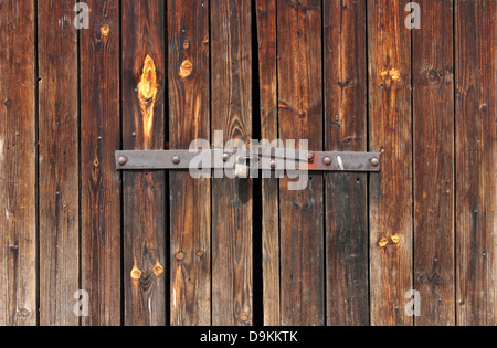 Old Wooden door locked with rusty padlock background. - Stock Photo
