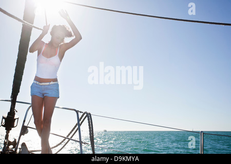 Young woman on yacht wearing shorts - Stock Photo
