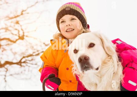 Girl with arm around dog - Stock Photo