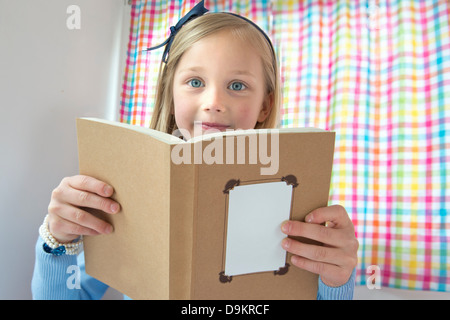 Portrait of young girl reading book - Stock Photo