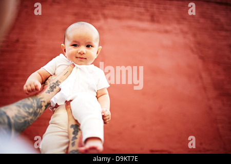 Father holding baby boy against red background, low angle view - Stock Photo