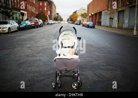 Baby boy asleep in push chair in middle of street - Stock Photo