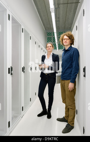 Two employees standing in data storage room - Stock Photo