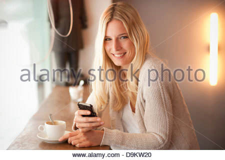 Portrait of young woman holding cellphone in cafe - Stock Photo