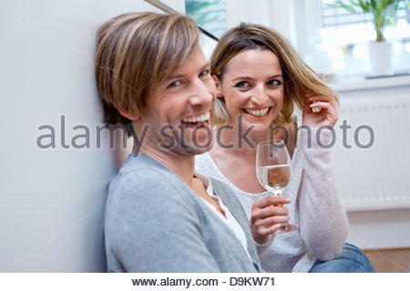 Couple in kitchen with wine - Stock Photo