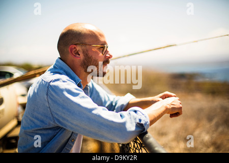 Mid adult man leaning on railing