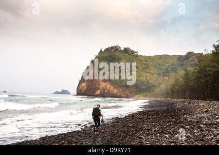 Mid adult man hiking along beach - Stock Photo