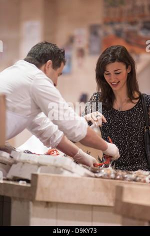 Woman buying fresh fish in market - Stock Photo