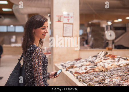 Woman looking at fresh fish in market - Stock Photo