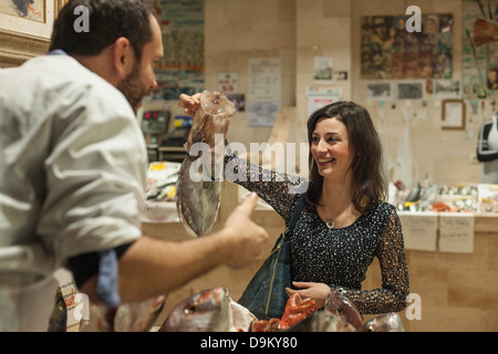 Woman buying fresh fish fishmonger - Stock Photo