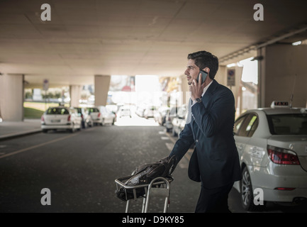 Young man on cell phone with luggage trolley in airport - Stock Photo