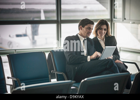 Businesspeople using digital tablet in airport departure lounge - Stock Photo