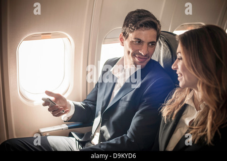 Businesspeople on aeroplane with smartphone - Stock Photo