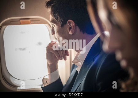 Male passenger looking out of aeroplane window - Stock Photo