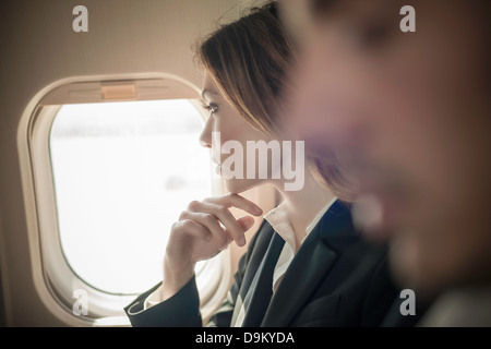 Female passenger looking out of aeroplane window - Stock Photo