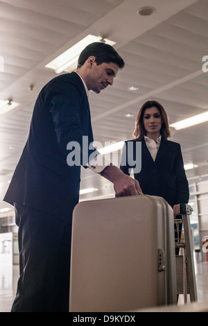 Businesspeople in airport with suitcase