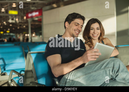 Young couple using digital tablet in airport departure lounge - Stock Photo