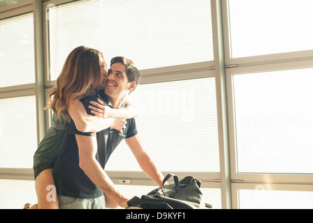 Young man giving woman piggy back in airport - Stock Photo