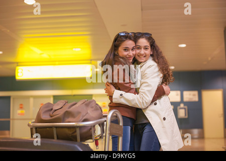 Two teenage girls hugging in airport - Stock Photo