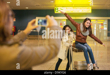 Woman photographing two teenage girls in airport - Stock Photo
