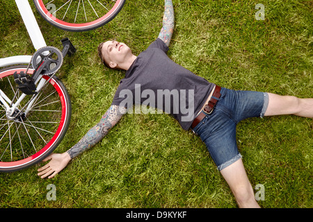 Young tattooed man lying on grass - Stock Photo