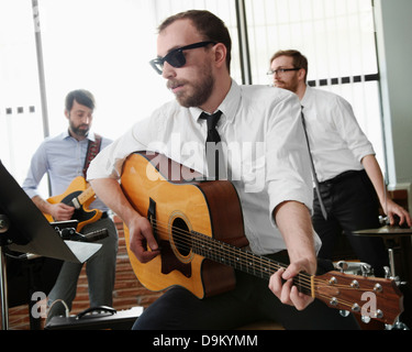 Young man playing guitar in rehearsal room - Stock Photo