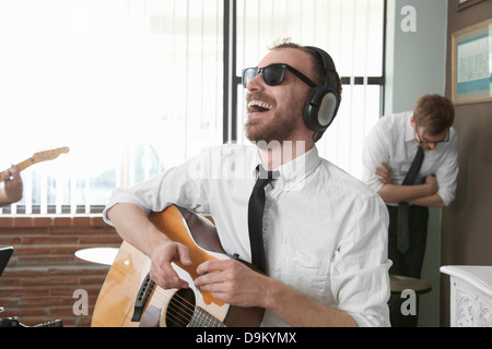 Young guitarist laughing in rehearsal room - Stock Photo