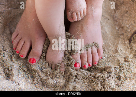 Mother with baby daughter's bare feet in sand - Stock Photo