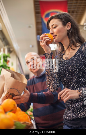 Woman smelling fresh oranges in market - Stock Photo