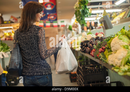 Woman shopping at greengrocer's in market - Stock Photo