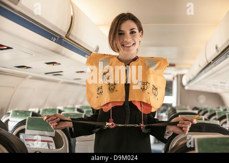 Air stewardess performing safety demonstration on aeroplane - Stock Photo
