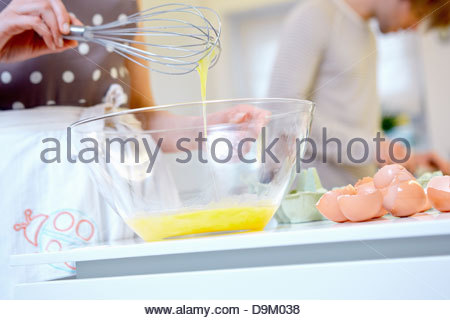 Woman whisking eggs in mixing bowl - Stock Photo