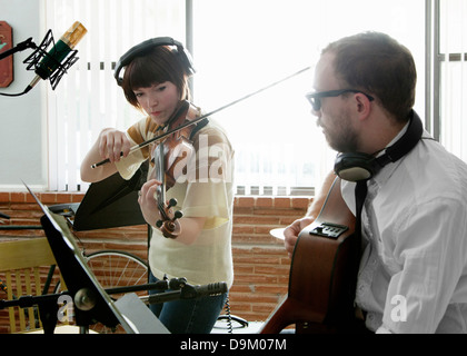 Young man and woman playing violin and guitar in music room rehearsal - Stock Photo
