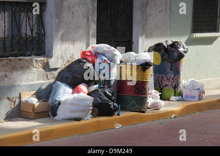 Piles of garbage blocking a sidewalk of the Casco Antiguo of Panama City.  Dirt filth filthy trash bins cans horrible - Stock Photo