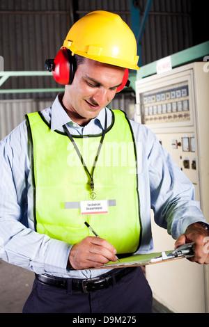 male industrial technician working inside a factory - Stock Photo