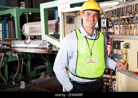 male Caucasian industrial technician portrait in front of machinery - Stock Photo