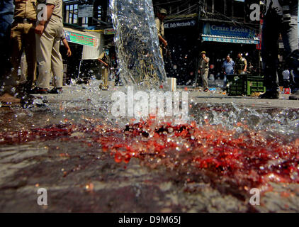Srinagar, Indian Kashmir. June 22, 2013 - Locals washing the blood stainmed road where two policemen were killed - Stock Photo