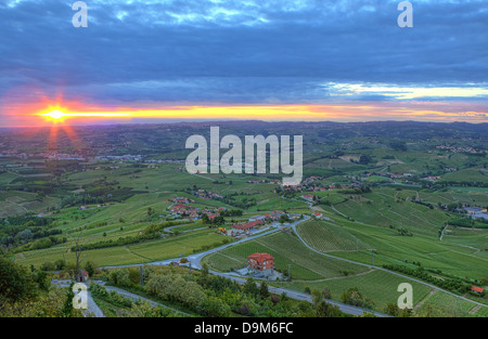 Aerial view on green hills and vineyards of Langhe under cloudy sky and rising sun early in the morning in Piedmont, - Stock Photo
